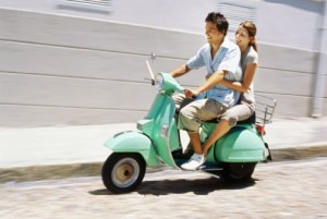 Young couple riding on a scooter and smiling