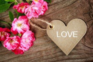Love message on heart shaped card with roses on wood background